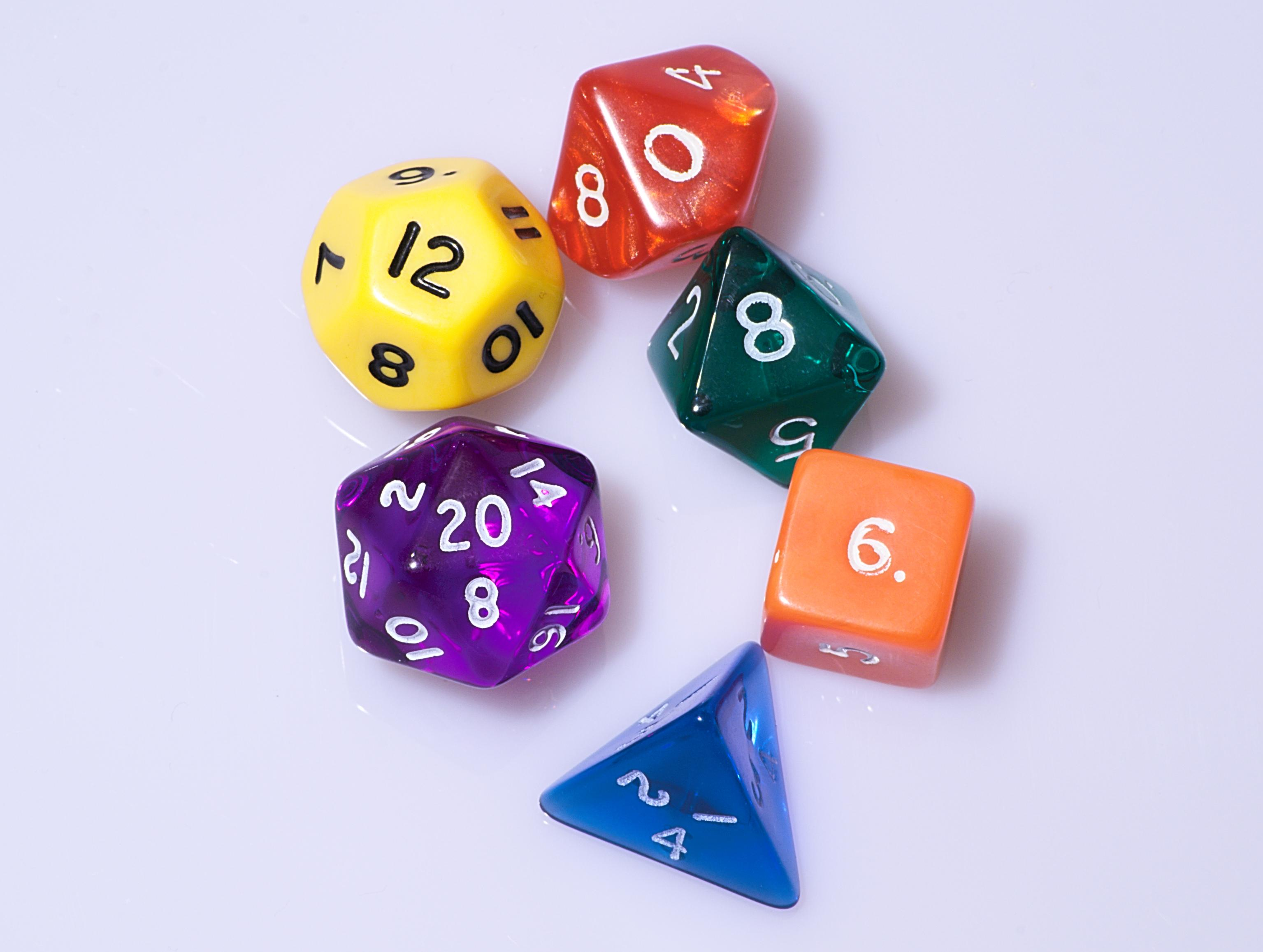 6 multicolored polyhedral dice on a white surface