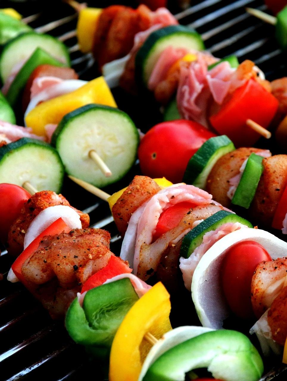 grill with kebabs of meat and veggies like peppers onion and zucchini