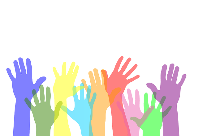 a group of multi-colored hands reaching up