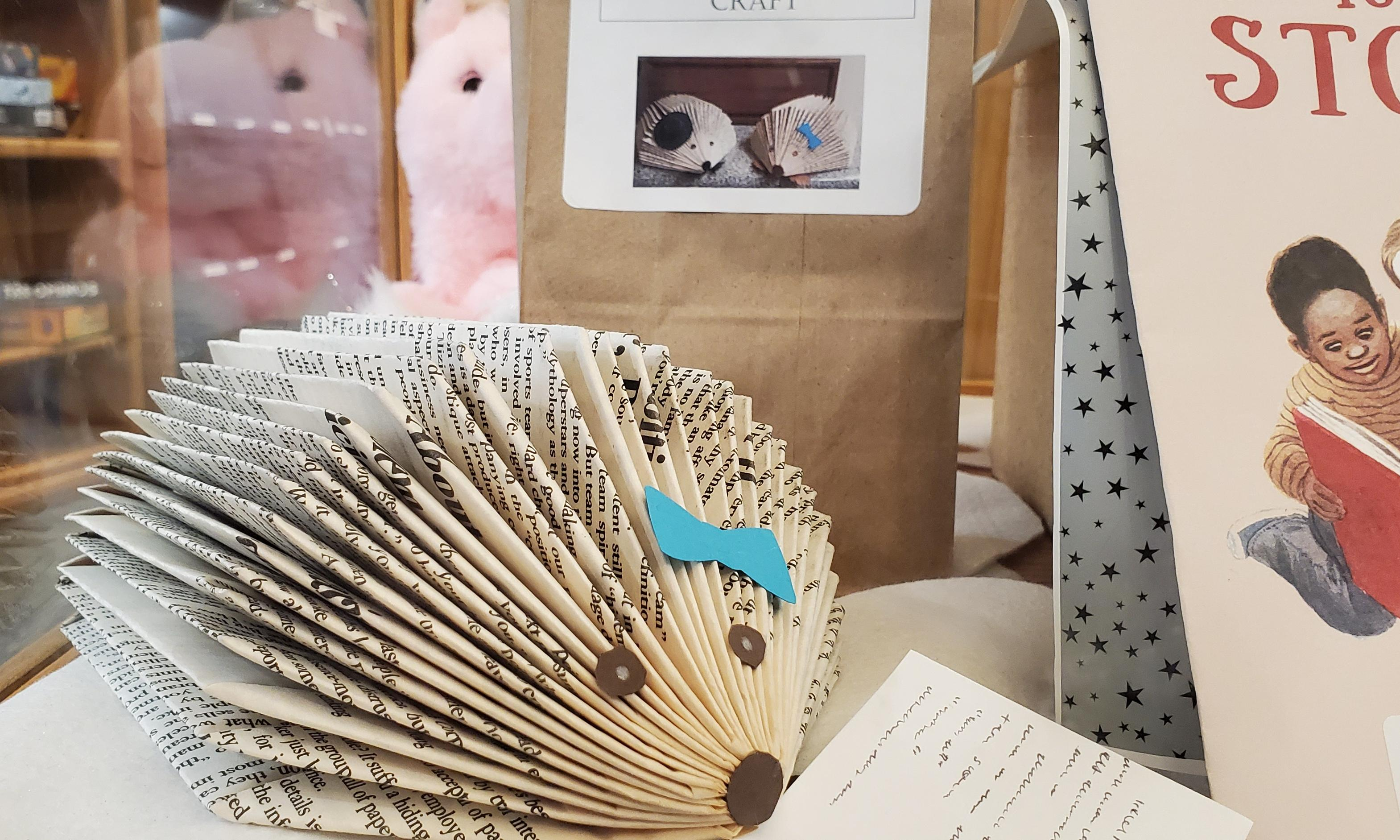 book folded into a hedgehog with a blue bow reading a book
